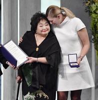 ノーベル平和賞の授賞式でメダルと賞状を授与され、顔を寄せ合うサーロー節子さん(左)とICANのベアトリス・フィン事務局長=10日、オスロ(共同)