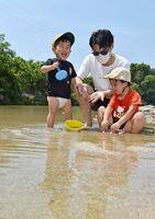 マスクを着けて、子供と水遊びをする父親=8日午後、佐賀市大和町の嘉瀬川(撮影・米倉義房)