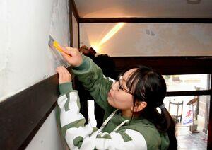 しっくいを塗り直すため、表面のペンキを削り取っていくボランティアたち=佐賀市松原の松川屋