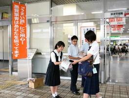 防止啓発のチラシとグッズを配布する高校生ら=佐賀市のJR佐賀駅