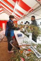 商売繁盛の縁起物とされる福笹を購入する参拝客(右)=佐賀市の佐賀恵比須神社