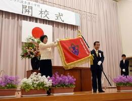 波多津小開校式で、塚部芳和市長(右)から新しい校旗を受け取った西山太佳子校長=伊万里市の同校