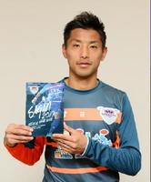 今季のオフィシャルイヤーブックを手にするFW池田圭選手