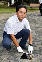 2007年に甲子園を制覇した佐賀北の記念プレートを設置する百﨑敏克さん=佐賀市城内のこころざしのもり