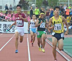 陸上男子1600メートルリレー予選 最後の直線で2位に浮上し、準決勝進出に貢献した鳥栖工のアンカー堤友希(左)=沖縄県のタピック県総ひやごんスタジアム