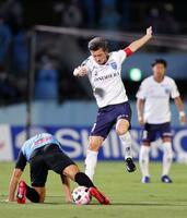 川崎戦に先発出場し、競り合う横浜FCの三浦知良(右)。サッカーJ1最年長出場記録を大幅に更新した=23日、川崎市等々力陸上競技場