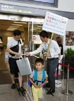 ポケットティッシュなどを手渡し、帰省客らにPRする職員ら=佐賀市の九州佐賀国際空港