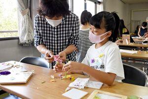 タイルに花を挟んで、押し花を作る子どもたち=唐津市の古代の森会館