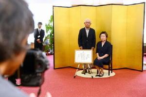 金びょうぶの前で記念撮影に収まる金婚さん夫婦=唐津市高齢者ふれあい会館りふれ