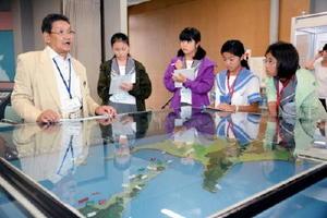 元島民の福沢さん(左)の引き揚げ当時の話を、地図を見ながら熱心に聞く生徒ら=北海道標津郡標津町の北方領土館