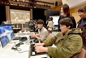 佐賀県内初の本格的なeスポーツ大会で、声援を受けながらプレーをする出場者=佐賀市のエスプラッツホール