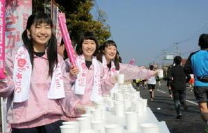 大会のタオルマフラーを首に掛け給水のボランティアに取り組む佐賀商業高校バトン部=佐賀市高木瀬西の10キロ地点給水所