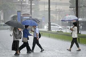 雨が降り続く鹿児島市内を傘を差して歩く人たち=6月