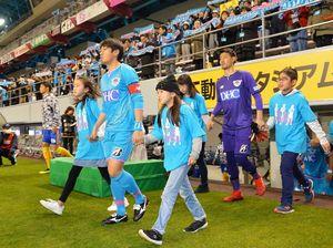 全国から集まった高橋さんと入場する高橋義希選手(左から2人目)ら鳥栖イレブン=鳥栖市の駅前不動産スタジアム