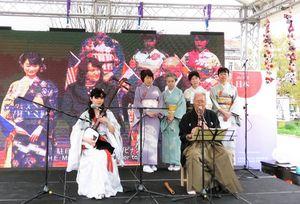 唐津での着物披露式典の映像をバックに、会員が尺八、三味線を演奏=4月13日、サラエボ市のハスタハナ公園(伊藤登志子さん提供)