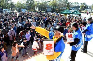 軽トラ市8周年を記念して行われた餅投げ。手前左は吉野ヶ里町商工会の宮原荘治会長=吉野ケ里歴史公園東口周辺