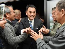 当選が確実となり、支援者に囲まれ笑顔を見せる峰達郎さん(中央)=29日午後10時33分、唐津市町田の事務所