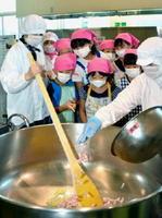 調理中の大きな釜をのぞき込む児童たち=多久市南多久町の市学校給食センター