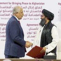 和平合意署名後に握手する米国のハリルザド・アフガニスタン和平担当特別代表(左)とタリバンのバラダル師=2020年2月、ドーハ