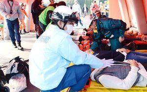 現場近くに設置したテントで患者の状態を調べるDMATメンバー=伊万里有田共立病院
