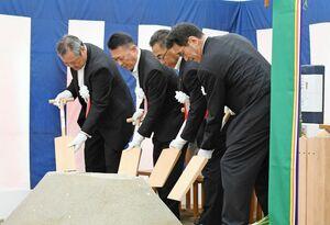 鋤で盛り砂を突く所作をする「穿初の儀」を行う出席者ら=佐賀市のSAGAサンライズパーク