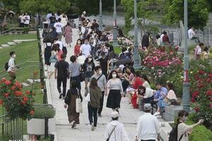 大阪市内の公園を歩くマスク姿の人たち=15日