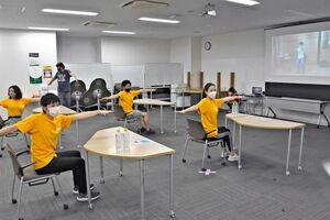 オンライン講習でリフレッシュ体操を実践するスタッフたち=鳥栖市弥生が丘のアマゾン鳥栖フルフィルメントセンター