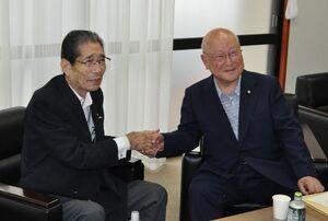 握手を交わす山田治雄氏(右)と髙松昭三氏=熱海市役所
