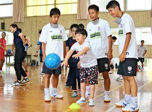 龍谷高生のサポートを受けながら、目標物にボールを投げる盲学校生=佐賀市の盲学校