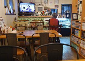 テレビで安倍首相の会見を見つめる中華料理店を営む女性。夕食の時間帯だが、客の姿はなかった=7日午後7時13分、佐賀市