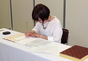 原爆死没者名簿に新たに死亡が確認された人の名前を書き加える森田孝子さん=28日午前、長崎市役所