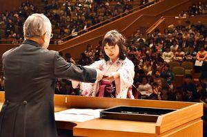 卒業証書を受け取る西九州大学の卒業生(右)=佐賀市文化会館