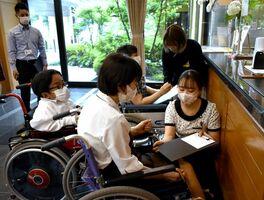 車いすを体験しながらチェックインの案内について確認する従業員ら=佐賀市高木瀬町の四季彩ホテル千代田館