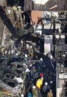 陸上自衛隊のAH64D戦闘ヘリの機体の一部(左上)が残る墜落現場を調べる自衛隊員ら=6日午前9時52分、佐賀県神埼市(共同通信社ヘリから)