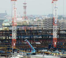 「SUNちゃん」「RISEさん」と名付けられた大型クレーン。SAGAアリーナの建設が続いている=佐賀市日の出のSAGAサンライズパーク周辺