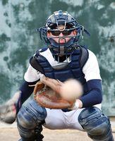 紫外線による視力低下を防ぐため、サングラスをして練習する伊万里高野球部捕手の梶山勇人さん=伊万里市の同校グラウンド