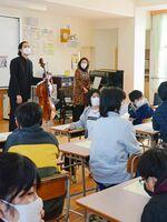 音楽室に掲げられた作曲家の肖像画を示しながら曲を紹介する笹沼樹さん=佐賀市の若楠小