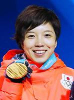 平昌冬季五輪のスピードスケート女子500メートルで獲得した金メダルを手に笑顔の小平奈緒=20日、韓国・平昌(共同)