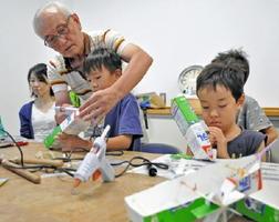 牛乳パックやゴムを材料に「凌風丸」の模型を作る子どもたち=佐賀市星空学習館