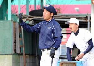 今春から佐賀北高で教壇に立つ久保貴大さん(左)。放課後には野球部副部長として、後輩たちの指導にあたる=同校グラウンド