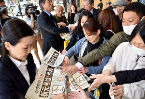 佐賀新聞社が発行した新元号の号外に殺到する人たち=午後0時26分、JR佐賀駅前