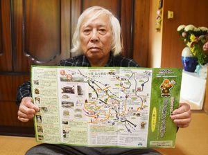 松浦党の史跡を巡るガイドマップを手にする峯博海さん=唐津市厳木町
