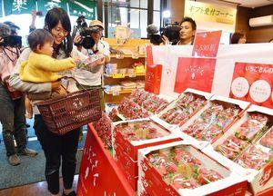 店頭に並んだ「いちごさん」を買い求める親子=15日午前、佐賀市大財のさが風土館季楽直販本店