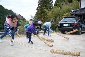 先の方にわらを巻いた竹で地面をたたき、モグラを追い払う子どもたち=唐津市相知町伊岐佐