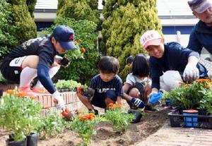 参加した子どもたちと花壇に花の苗を植える鹿島実業高校の生徒たち=鹿島市高津原