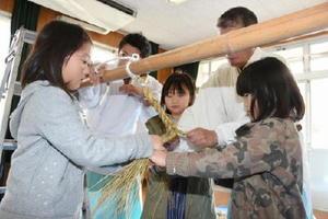 真剣な表情でしめ縄作りに取り組む子どもたち=佐賀市の若楠公民館