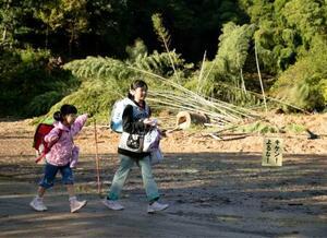 再開した耕野小学校に登校し、台風19号による土砂が流入した跡が残る校庭を歩く児童=23日午前7時36分、宮城県丸森町