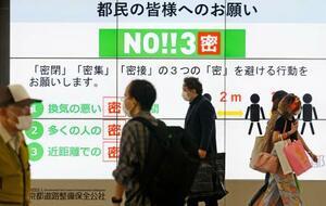「3密」を避ける行動を呼び掛ける大型モニターの前を歩く人たち=26日午前、東京都新宿区