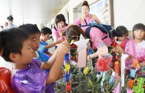 ササに飾り付ける園児ら=JR佐賀駅