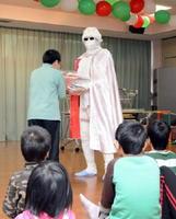 月光仮面の格好をした鬼塚吉隆さんにプレゼントをもらう子どもたち=佐賀市の清光園